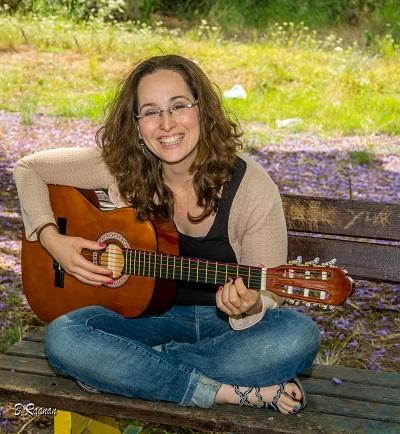 הדס מנגנת על גיטרה בספסל בטבע כשהיא יושבת
