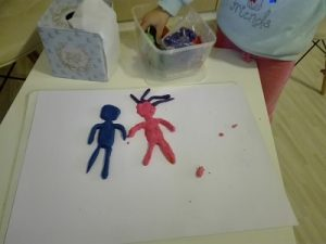 2 דמויות עשויות בצק משחק על דף ומעט מילד שעומד ליד
