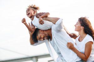 אבא מרים ילד צוחק ואמא תומכת - משפחה שמחה