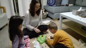 הדס יושבת בסלום ומשחק משחק לוטי קרוטי עם שני ילדים כבני 5
