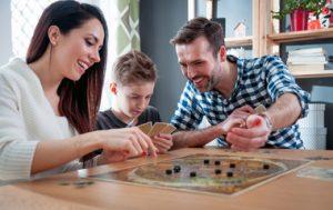 אבא ואמא וילד משחקים משחק לוח על שולחן