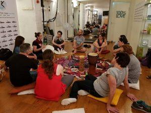 מבוגרים סביב שטיח עם כלי נגינה והדס מנחה בסדנה בקלימבה בתל אביב