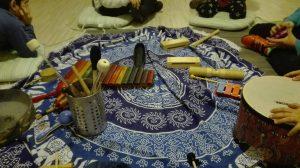 כלי נגינה על שטיח וילדים סביב מתוך קבוצה חברתית