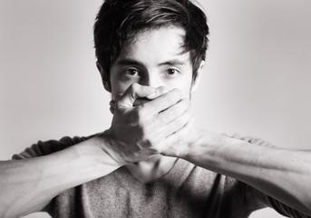 נער מכסה את פניו בידיו