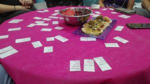 שולחן עליו קלפים עם מילות שירים ומסביב לשולחן אנשים- סדנה של הדס
