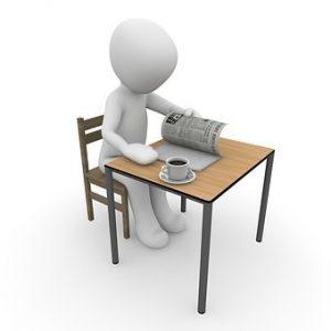 דמות ללא זהות יושבת ליד שולחן קוראת עיתון וקפה לידה