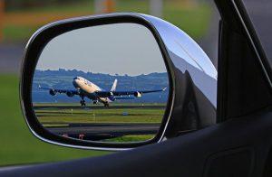 תמונות מראה של מכונית בה משתקף מטוס ממריא