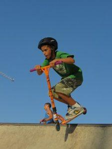 ילד בן כ10 שקופץ על קורקינט מעל גדר